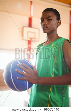 Portrait of teenager with basketball standing in court