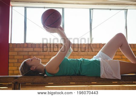 Side view of woman playing with basketball while lying on bench in court