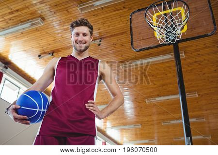 Portrait of male basketball player standing by basketball hoop in court