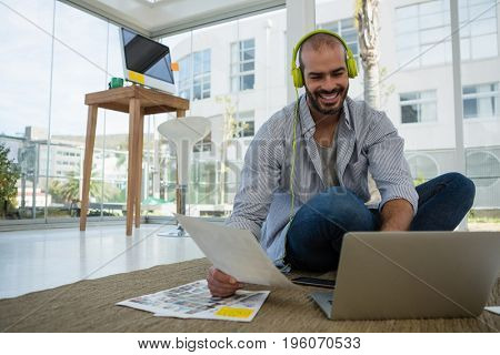 Smiling desginer holding collage using laptop while sitting on floor at workshop