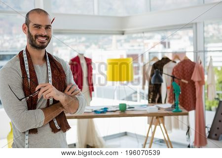 Portrait of smiling designer with arms crossed standing in workshop