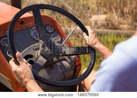 Close-up of woman driving tractor in olive farm on a sunny day