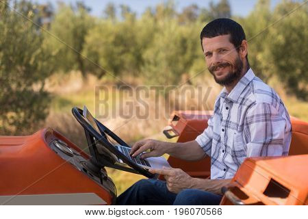 Portrait of happy man using laptop in tractor on a sunny day