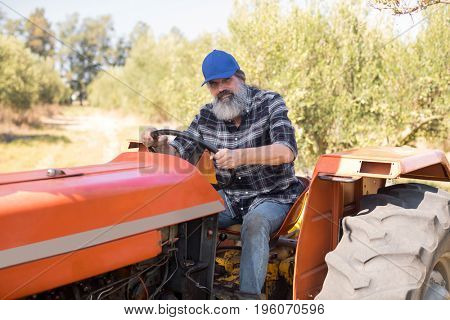 Portrait of confident man sitting in tractor on a sunny day