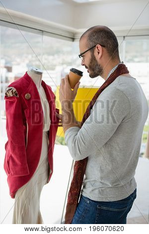 Designer examining clothes while drinking coffee at studio