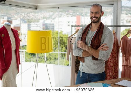 Portrait of smiling male designer with arms crossed standing by clothes rack at studio