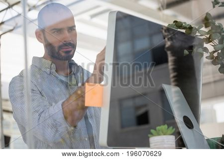 Male designer using computer while standing in studio seen through glass