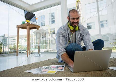 Smiling desginer using laptop while sitting on floor at studio