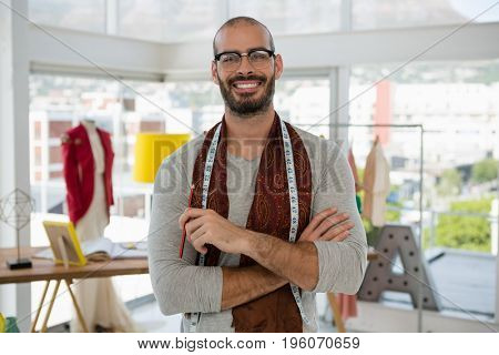Portrait of smiling male designer with arms crossed standing in studio