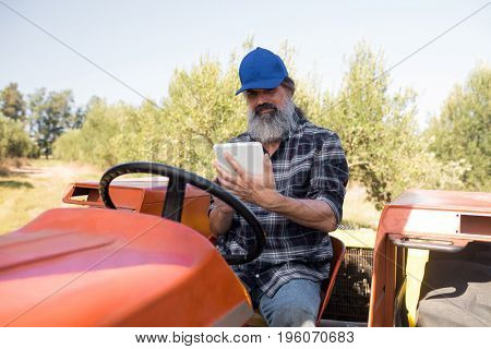 Man using digital tablet in tractor on a sunny day