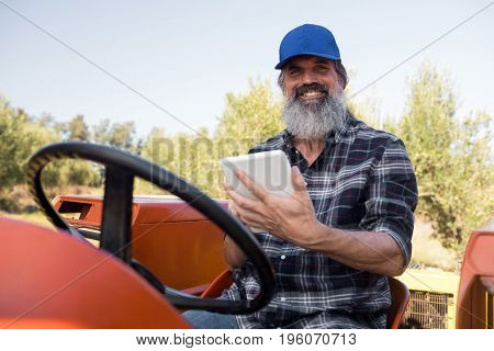 Portrait of happy man using digital tablet in tractor on a sunny day