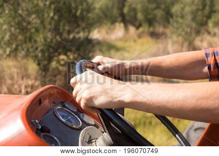 Close-up of man driving tractor in olive farm on a sunny day