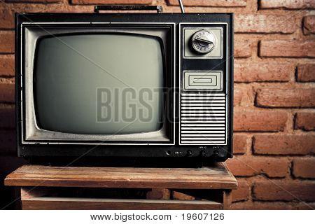 Retro Grunge Tv Against Brick Wall.