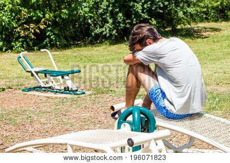 young man in break during workout outside in the park