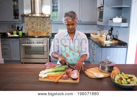 Woman cutting vegetables while preparing food in kitchen at home