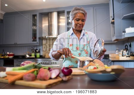 Senior woman preparing food in kitchen at home