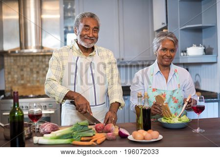 Portrait of senior couple preparing food in kitchen at home