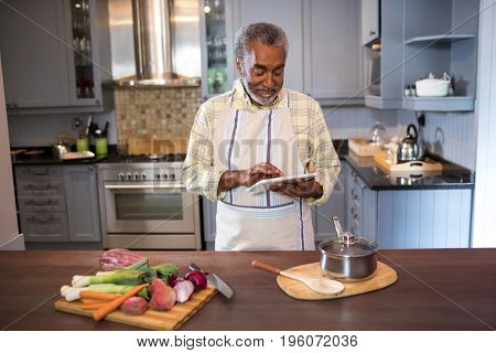 Smiling man using tablet computer while cooking food in kitchen at home