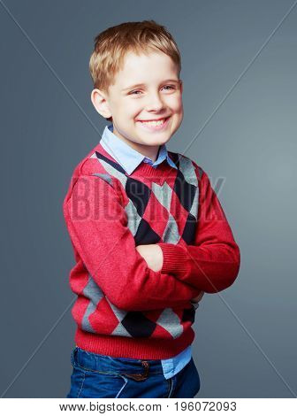 happy excited laughing child wearing a sweater  isolated against grey background