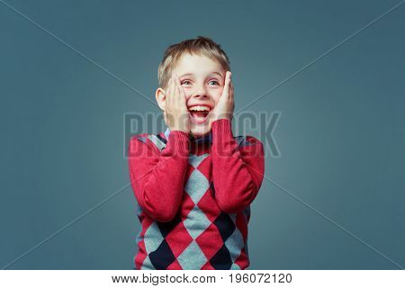 happy excited child wearing a sweater  isolated against grey background