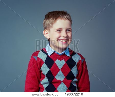 happy laughing child wearing a sweater  , isolated against grey background