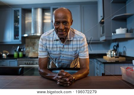 Portrait of senior man with hands clasped leaning on table in kitchen