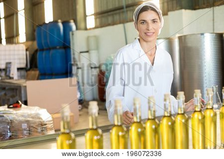 Portrait of happy worker standing at table in factory