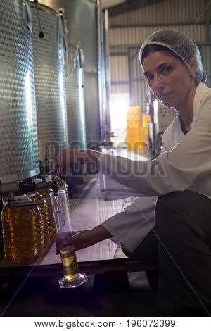 Portrait of female technician examining olive oil in factory