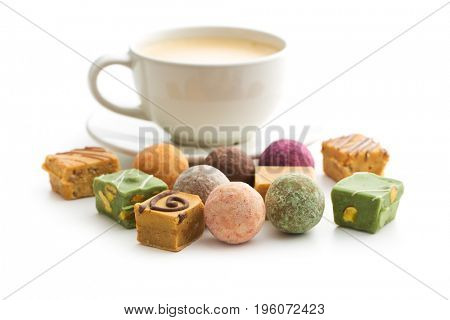 Various sweet candies and coffee cup with coffee.