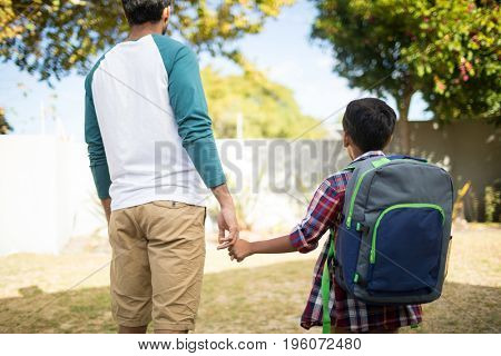 Rear view of father holding hand of son with backpack while standing in yard