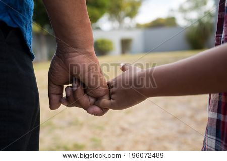 Close up of grandfather and grandson holding fingers while standing in yard
