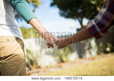 Cropped image of father and son holding hands while standing in yard