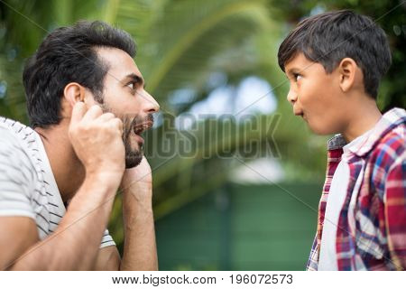 Side view of father and son making faces while playing in yard