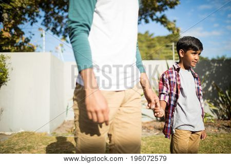 Father and son holding hands while standing in yard during sunny day