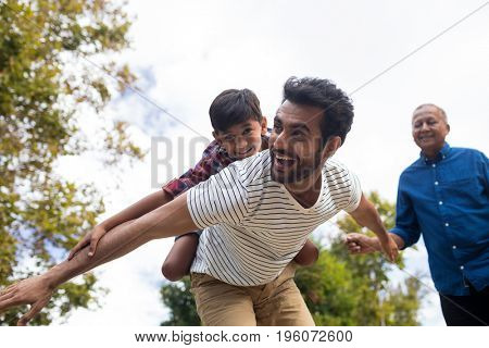 Happy grandfather looking at man giving piggy backing to son with arms oustretched in yard