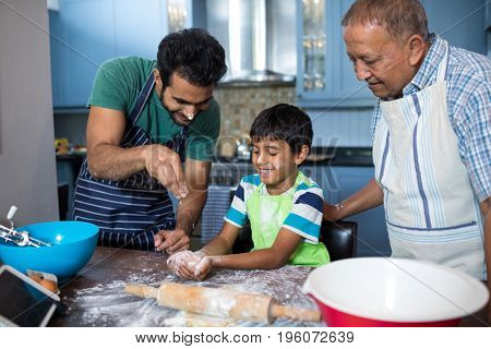 Father sprinkling flour on sons hand while preparing food with grandfather in kitchen at home