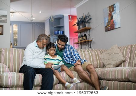 Family using digital table while sitting on sofa in living room at home