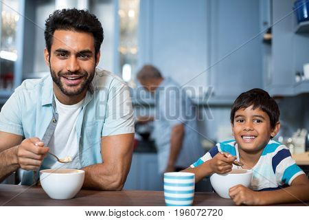 Portrait of father and son having breakfast at table with man in background