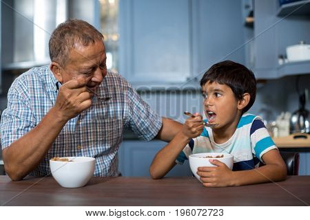 Grandfather and grandson having breakfast at home
