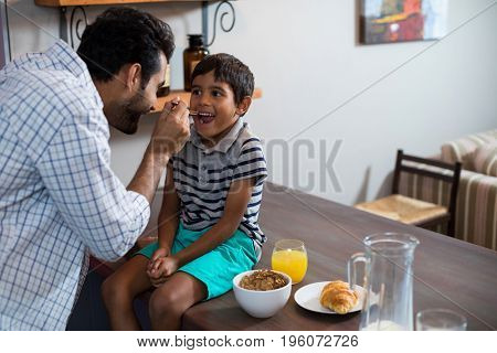 Happy father feeding cereal breakfast to son sitting on table at home