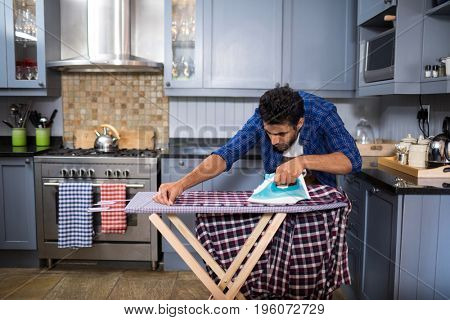 Young man ironing shirt on board in kitchen at home