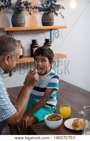 Grandfather feeding grandson sitting on table at home