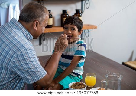 Happy grandfather feeding grandson sitting on table at home