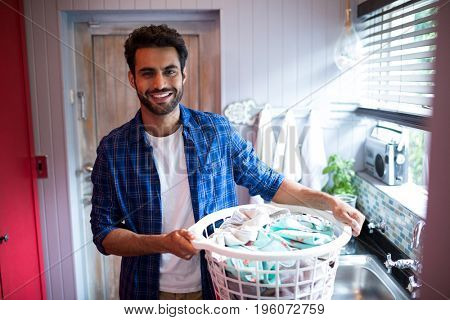 Portrait of smiling young man holding laundry basket while standing by window at home