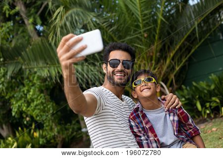 Father and son wearing sunglasses while taking selfie through phone in yard