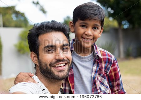 Close up portrait of happy father and son in yard