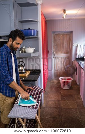 Side view of man ironing shirt on board at home