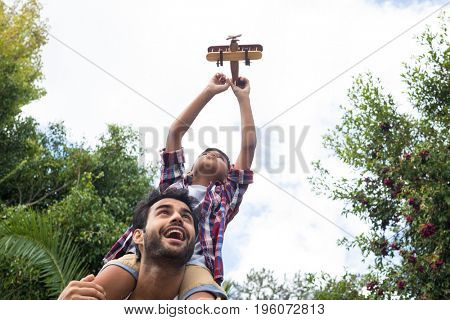 Low angle view of father carrying son playing with airplane in yard