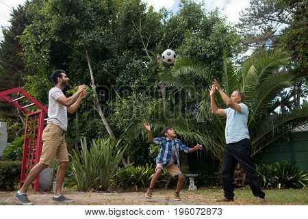 Family playing with soccer ball against plants at park
