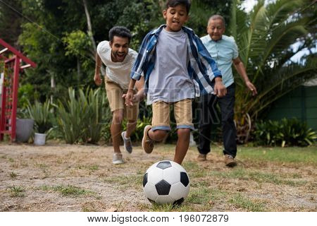 Happy boy playing soccer with father and grandfather in yard